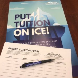 Photo of pen and petition atop a poster for the tuition freeze campaign